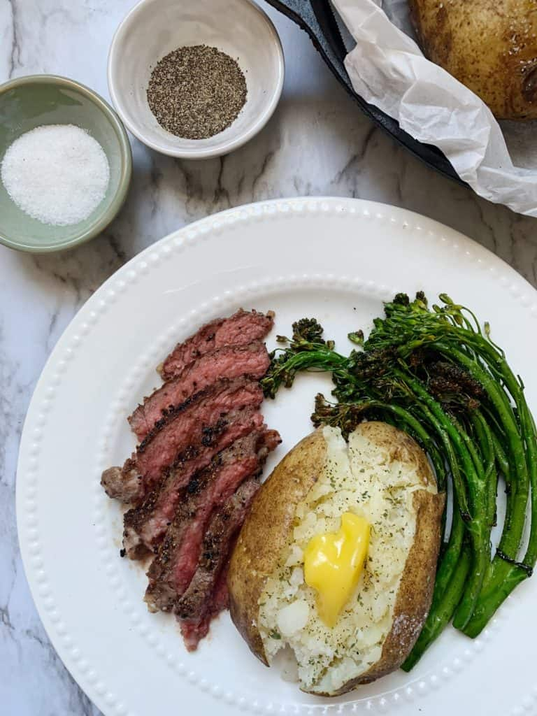 Instant Pot Baked Potatoes on a plate with sliced steak and baby broccoli
