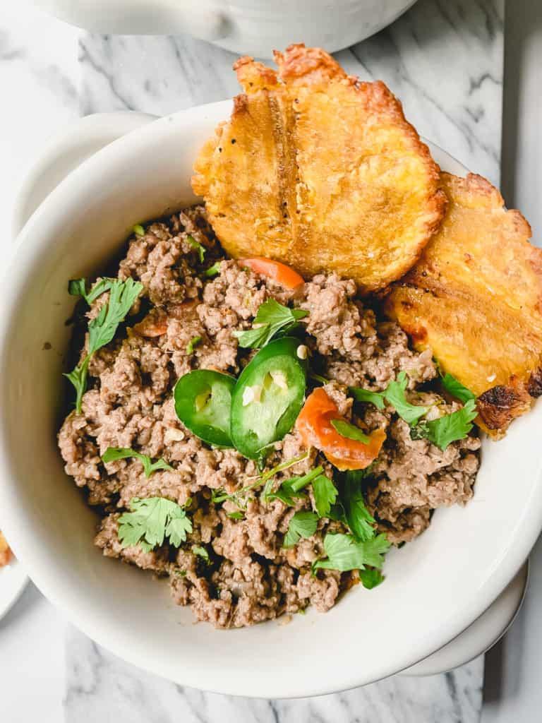 a bowl of lamb keema & garlic tostones