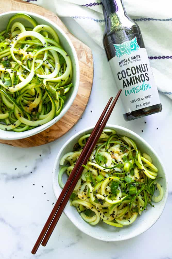 cold sesame wasabi noodles next to a bottle of wasabi coconut aminos