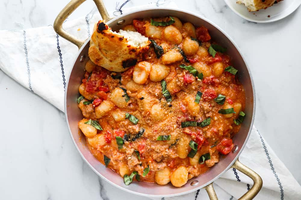 creamy spicy sausage gnocchi in a skillet with a crusty piece of bread dipped in the sauce