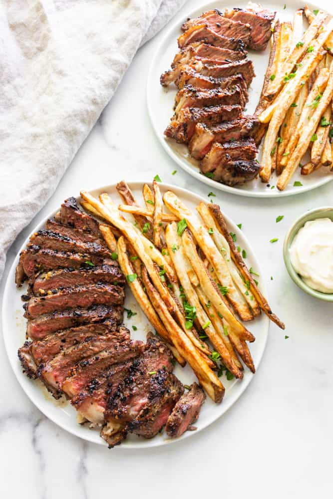 two plates of steak frites with garlic mayo dip