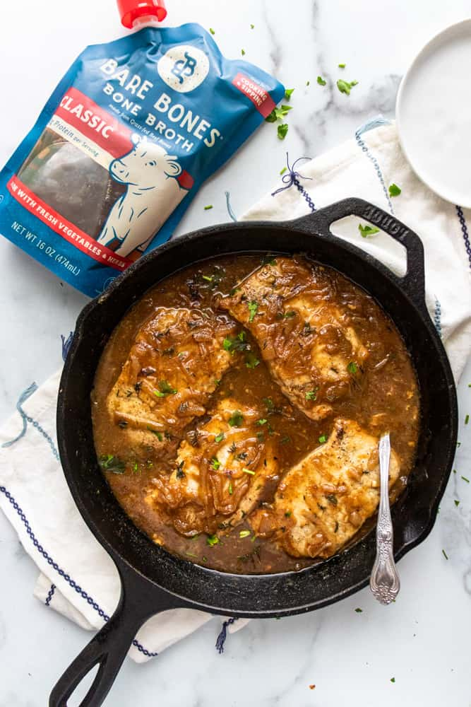 french onion smothered pork chops in a skillet