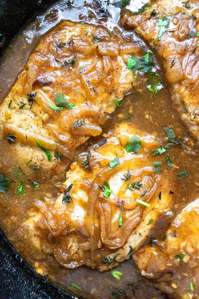 french onion smothered pork chops up close in a skillet