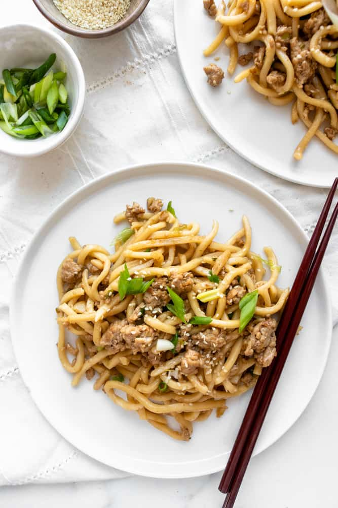 sesame ginger udon stir fry on a plate with chopsticks