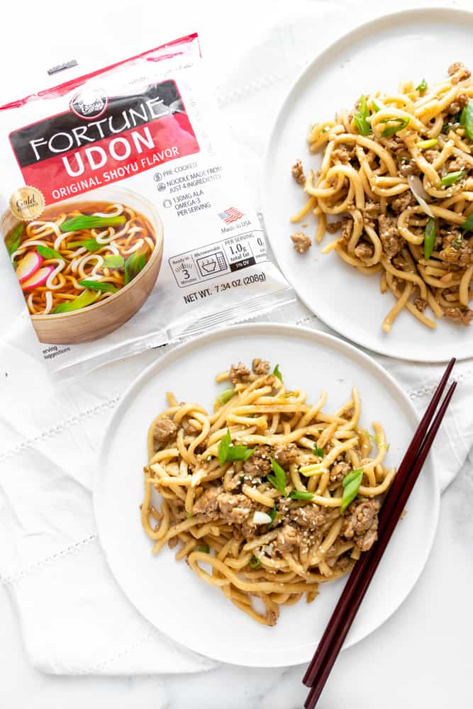 two plates of sesame udon stir fry with the packaging of the udon noodles next to them