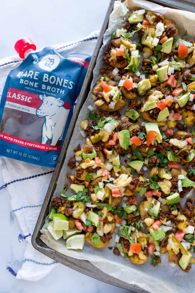 crispy smashed potato nachos on a tray next to a package of bare bones broth