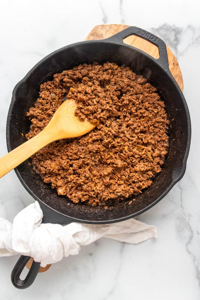 ground taco meat in a cast iron skillet with a wooden spoon in it