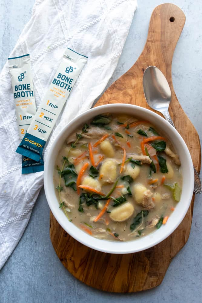 a bowl of chicken gnocchi soup next to two packets of instant beverage mix