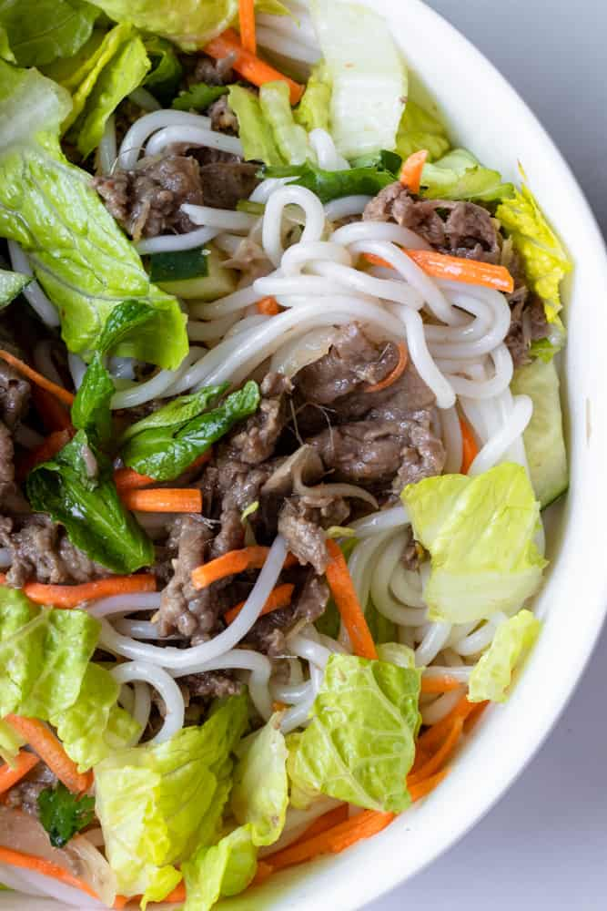 a bowl of bun bo xao (vietnamese lemongrass beef noodle) mixed