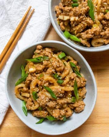 two bowls of peanut garlic udon stir fry next to chopsticks