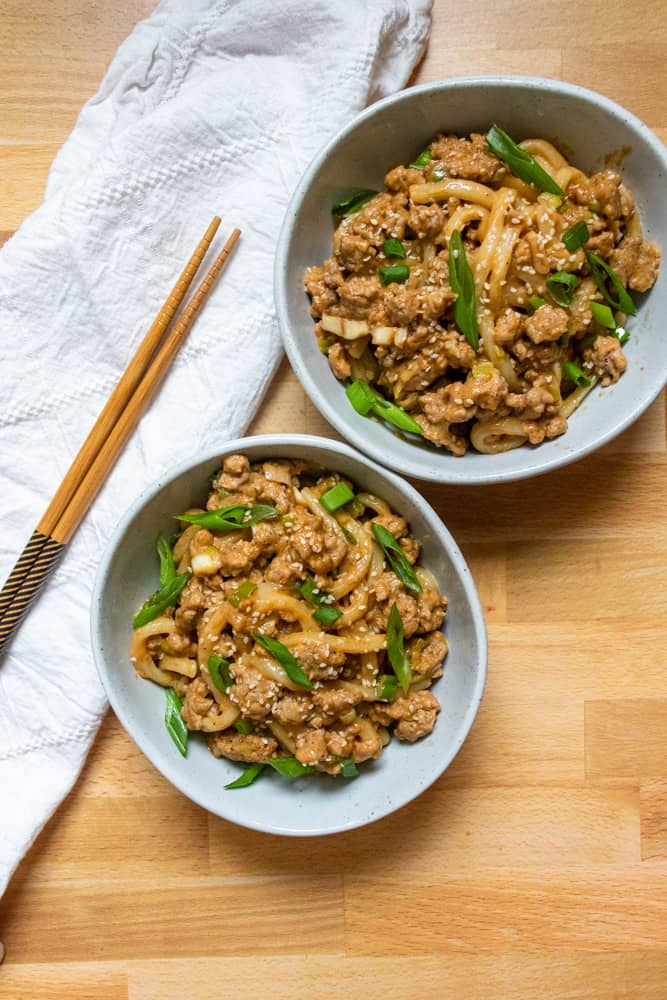two bowls of peanut garlic udon stir fry