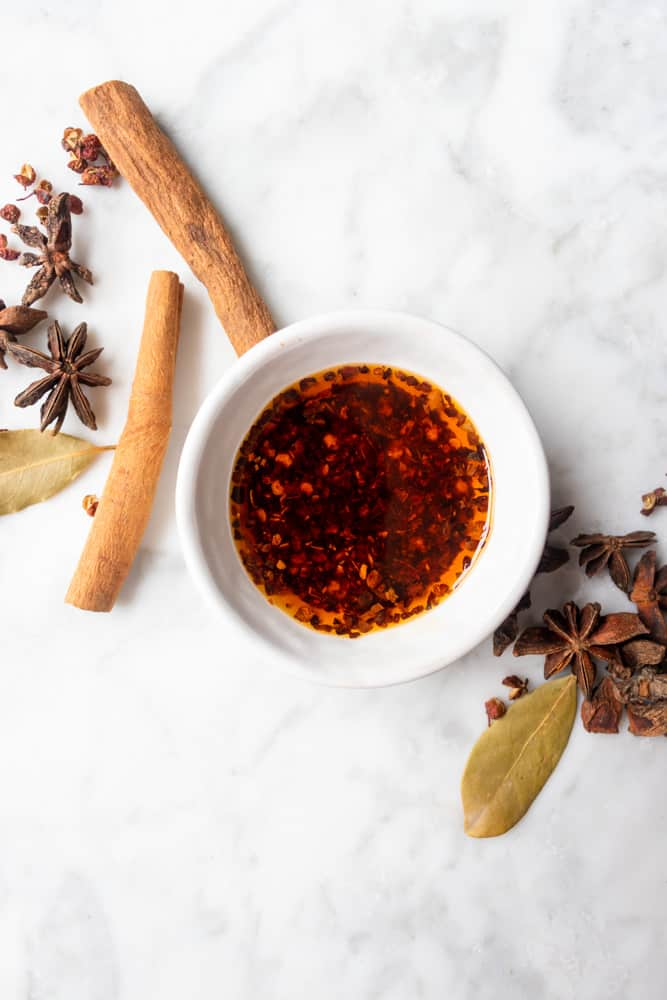 hot chili oil in a small bowl next to aromatics
