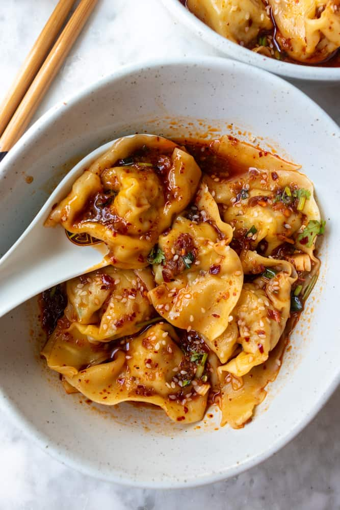 Spicy Szechuan Wontons in a bowl and one if being held in a soup spoon