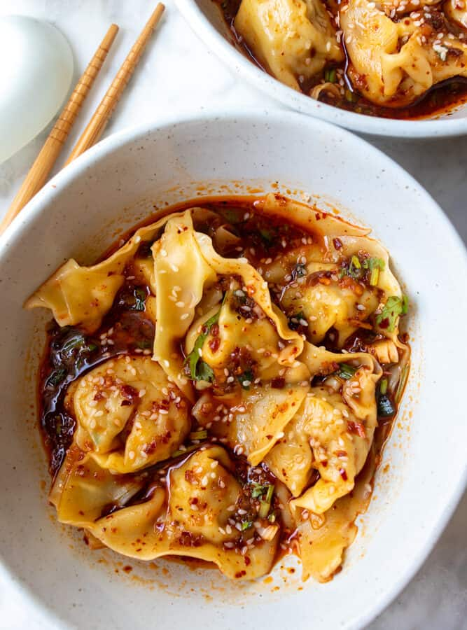a bowl of Spicy Szechuan Wontons next to another bowl with chopsticks and a spoon