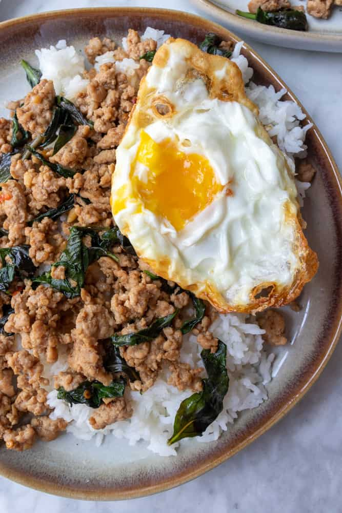 close up of a crispy fried egg on top of the Pad Kra Pao
