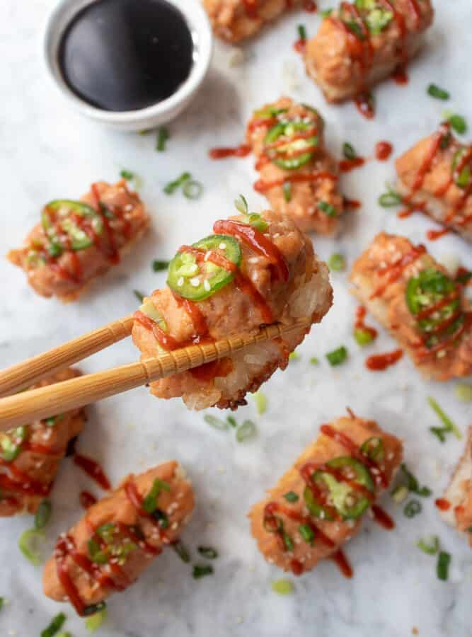 one Spicy Tuna Crispy Rice held up by a pair of chopsticks