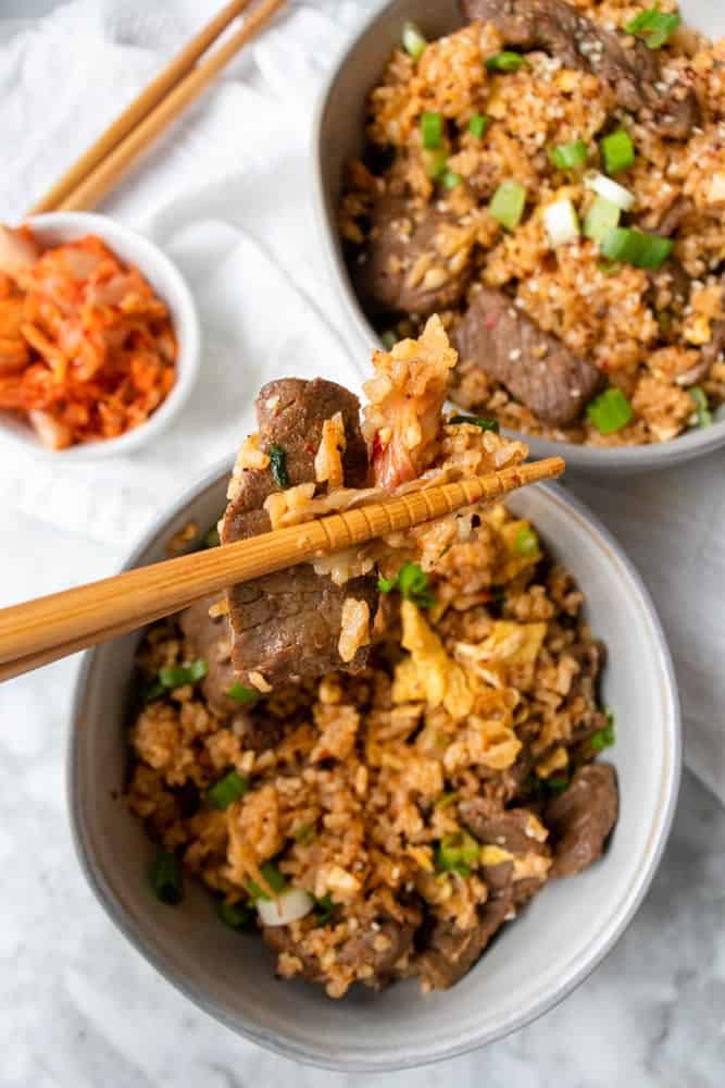 Bulgogi Kimchi Fried Rice in a bowl and a piece of steak help up by chopsticks