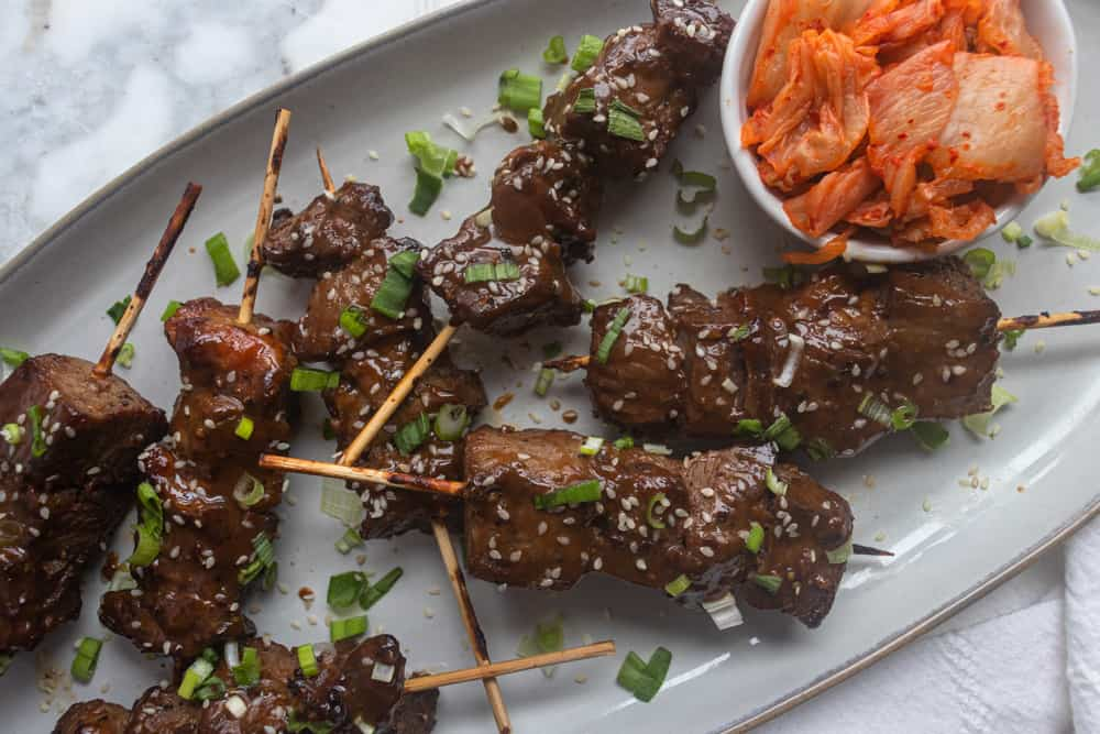 Korean BBQ Skewers on a platter next to a bowl of kimchi