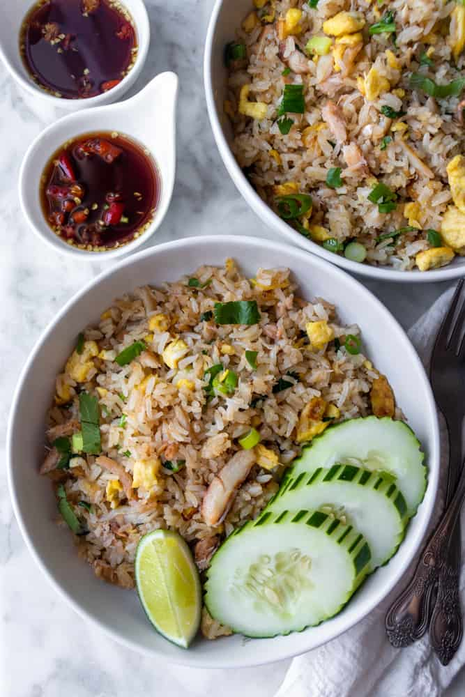 Two bowls of Thai Crab Fried Rice with cucumber slices and nam prik pla